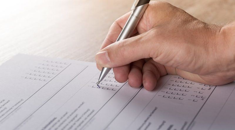 Blurred photo of a survey being filled out. Hand with pen.